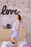 Femme mignonne enceinte portant la robe bleue tenant le ventre, amour d'inscription sur le mur de briques Image stock