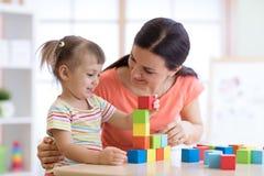 Femme mignonne et enfant jouant les jouets éducatifs au jardin d'enfants ou à la pièce de crèche Image libre de droits