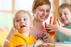 Femme mignonne jouant et peignant avec des enfants photo stock