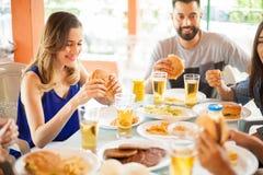Femme mignonne mangeant un hamburger avec des amis Photos stock