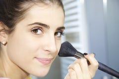 Femme mignonne mettant le maquillage souriant regardant la caméra photo stock