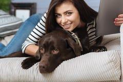 Femme mignonne positive s'amusant et son animal familier photo stock