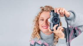 Femme mignonne prenant une photo avec une caméra sur un fond blanc photos libres de droits
