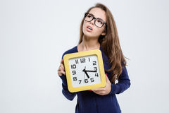 Femme mignonne réfléchie tenant l'horloge murale Images libres de droits
