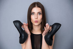 Femme mignonne tenant des chaussures au-dessus de fond gris Photos stock