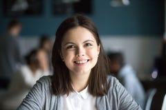 Femme millénaire de sourire regardant l'appareil-photo dans le lieu public, tête photo libre de droits