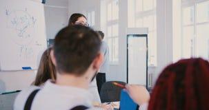 Femme millénaire positive d'entraîneur d'affaires parlant aux travailleurs multi-ethniques heureux lors du cours de formation Lie banque de vidéos