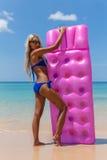Femme mince avec le matelas rose de natation sur la plage tropicale Photographie stock libre de droits