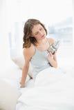 Femme mince contrariée s'asseyant sur son lit sous la couverture Images stock