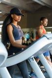 Femme mince d'afro-américain sexy avec son entraîneur sportif bel noir sur le tapis roulant dans le gymnase Concept de forme phys Image stock