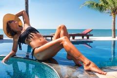 Femme mince dans le chapeau de paille de s et le bain de soleil de lunettes de soleil Photographie stock