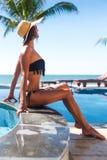 Femme mince dans le chapeau de paille de s et le bain de soleil de lunettes de soleil Images stock