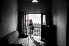 Femme mince dans un peignoir, se tenant sur le balcon Image stock