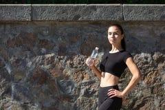 Femme mince de coureur dans la bouteille d'eau de participation d'usage de sport L'espace pour le texte photographie stock