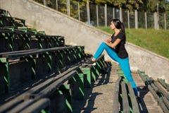 Femme mince de forme physique étirant des jambes avant le fonctionnement au stade L'espace pour le texte images stock