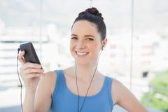 Femme mince de sourire écoutant la musique Images stock