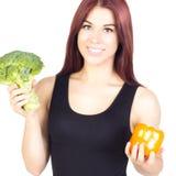 Femme mince de sourire tenant les poivrons et le brocoli Régime et prope Photographie stock libre de droits