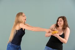 Femme mince essayant d'arrêter son ami vaillant de manger des puces sur le fond de couleur Concept de nourriture de r?gime photos libres de droits