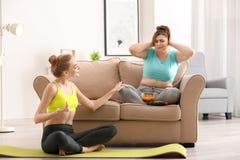 Femme mince offrant son ami vaillant pour joindre la séance d'entraînement au lieu de manger de la nourriture malsaine à la maiso photographie stock