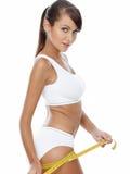 Femme mince sûre mesurant ses cuisses Images stock