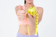 Femme mince tenant la pomme avec la bande de mesure image libre de droits