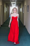 Femme modèle blonde de beauté en égalisant la robe rouge Photographie stock