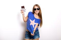Femme modèle de beauté dans des lunettes de soleil mangeant du chocolat foncé La belle jeune femme étonnée prend des bonbons à ch Image libre de droits