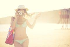 Femme moderne à la mode de hippie d'ajustement attrayant prenant des photos avec le rétro appareil-photo de film de vintage Photo photo libre de droits