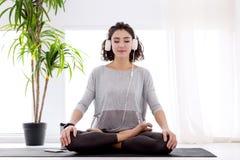 Femme moderne avec des ?couteurs se reposant dans la posture de lotus de yoga photo libre de droits