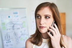 Femme moderne ayant l'appel téléphonique dans le bureau photo stock