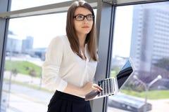 Femme moderne d'affaires dactylographiant sur l'ordinateur portable tout en se tenant dans le bureau avant de se réunir ou présen Photographie stock