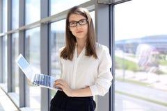 Femme moderne d'affaires dactylographiant sur l'ordinateur portable tout en se tenant dans le bureau avant de se réunir ou présen Images libres de droits