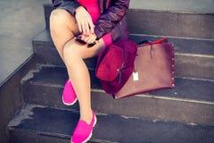 Femme moderne dans des espadrilles se reposant sur des escaliers Photo stock