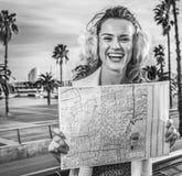 Femme moderne de sourire sur le remblai à Barcelone, Espagne avec la carte Photographie stock libre de droits