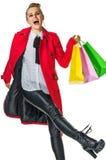Femme moderne gaie dans le manteau rouge sur le blanc avec des paniers photos stock