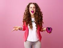 Femme moderne heureuse avec les bonbons au chocolat en forme de coeur dans la bouche Photo stock