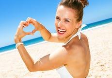 Femme moderne heureuse sur le bord de la mer montrant les mains en forme de coeur Photo stock