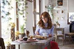 Femme moderne s'asseyant dans le café images stock