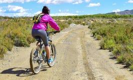Femme montant un vélo de montagne par un chemin boueux de la saleté photo stock