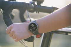 Femme montant un vélo et employant le smartwatch photo libre de droits