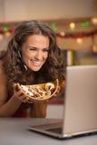Femme montrant des biscuits de Noël tout en ayant la causerie visuelle sur l'ordinateur portable Photo libre de droits