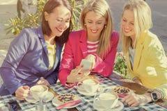 Femme montrant des photos à ses amis au téléphone portable Image libre de droits