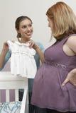 Femme montrant des vêtements de bébé à un ami enceinte Photo libre de droits