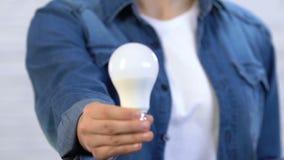 Femme montrant la lampe de LED sur la caméra, l'économie d'énergie et l'économie, sécurité de planète clips vidéos