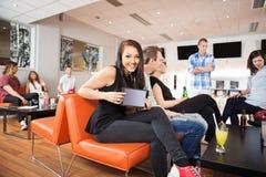 Femme montrant la Tablette de Digital dans le bowling Images stock