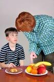 Femme montrant le fruit à un jeune garçon Photo stock