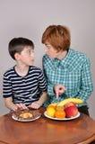 Femme montrant le fruit à un jeune garçon Photos libres de droits