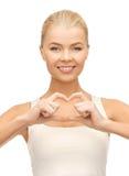 Femme montrant le geste de forme de coeur Photographie stock