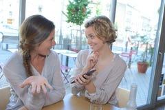 Femme montrant le téléphone portable à l'ami dans le restaurant Photographie stock