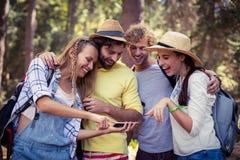 Femme montrant le téléphone portable aux amis Photos stock